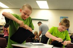 Fourth graders William Ramirez, 9, and Davis Nelson, 9, apply a protective sleeve to an Apple iPad during the first day of the 2013-2014 school year Aug. 1 at Falcon Elementary School in Falcon School District 49. Falcon Zone received 230 iPads for a one-to-one pilot program at the elementary school, according to fourth grade teacher Jarrod Torrez, who helped setup the devices. Students in third though fifth grades will receive the tablet PC, which they'll be able to take home.