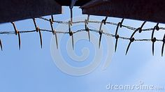 Low angle view looking to the top of a silhouetted iron wall with barbed wire, blue sky background.