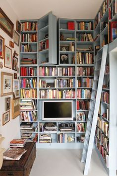 Cute book nook with hidden compartments -- there's a bunk bed behind those blue cabinets!