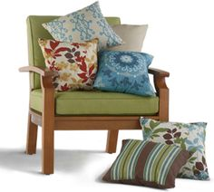 Patio chair covered with various patterned pillows love the colors