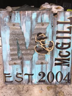 """Free pallet: reconstructed into a sign, stained and painted with letters printed out and colored onto the pallet with a sharpie. Free corrugated metal from the pasture, cut out with metal shearers for the """"M"""". The anchor was also cut out of corrugated metal and spray painted a rustic charcoal."""