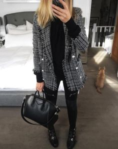 A tweed blazer with a black knit, black jeans, and embellished boots.