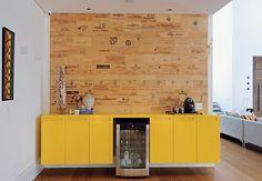 Para revestir a parede da sala de almoço, a arquiteta Luita Trencha apostou em uma ideia diferente: pedaços de madeira levam a impressão de diferentes rótulos de vinhos