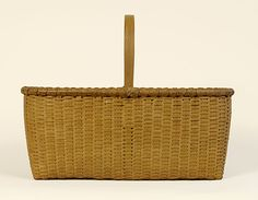 "A superior example of the art of Shaker basket weaving.  Ash and maple retaining an old or original taupe wash.  Essentially the basket equivalent of a Shaker carrier.  New Lebanon, New York.  Circa 1850.  Height to rim, 6 1/2"", height to top of handle, 11"", length, 14 1/2"", width, 9 3/8""."