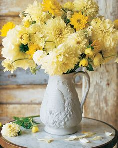 Assorted yellow flowers in white water pitcher.