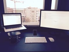 Clean workdesk with Macbook on elevated level and second display, seamless and clean
