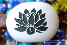 Carved Mani Stone with Lotus. The lotus flower grows in muddy water and rises above the surface to bloom with remarkable beauty. At night the flower closes and sinks underwater, at dawn it rises and opens again. Untouched by the impurity, lotus symbolizes the purity of heart and mind. The lotus flower represents long life, spiritual awakening, health, honor and re-birth. The Lotus flower brings good luck.