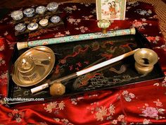 This simple but rather colorful opium smoking layout is displayed on a lacquered tea tray. One pipe is crafted with a Canton enamel stem, and the other is made from a solid piece of ivory. Beyond the tray are a lacquered bowl stand with a collection of blue-and-white porcelain bowls, and a polychrome porcelain opium pillow.