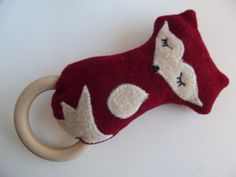 Wool + Wood Fox Baby Rattle and Teething Ring    Proudly made 100% in the USA. Absolutely nothing synthetic. All natural and completely non-toxic baby rattle with wooden teething ring. Made using repurposed wool from felted sweaters and wool blanket remnants for the backing. The wood is sourced from the USA. Inside is a bell and wooden beads. This toy is perfect for young babies to grasp and completely safe for babys mouth. The natural qualities of wool make it resistant to mold and mildew…