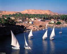 Stunning panorama: Feluccas on the Nile as Aswan with the necropolis visible in the background