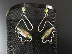 Green pairs beautifully with silver. These one-of-a-kind long dangle earrings are inspired by Greenery, Pantones chosen color for 2017. Flecks of silver and the odd crystal add individual flair to each of the tubular shaped Artisan glass beads (*). Silver plated metal wire is shaped, then hammered for texture. Gunmetal rondels add pattern to the mix. Small green acrylic beads add color and interest to the ear wire without additional weight. Truly a uniquely designed gift. * Please note that… Acrylic Beads, Jewelry Collection, Greenery, Dangle Earrings, Glass Beads, Dangles, Artisan, Wire, Texture