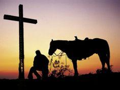 Sunset cowboy kneeling at cross