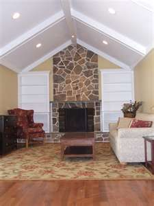 stone fireplace, white beams, book shelves