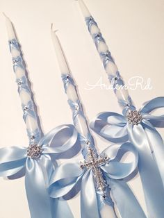 Beautiful set of (3) tapered candles wrapped in satin ribbon and crystal finished with a bow and crystal cross center on the large candle and a crystal cluster brooch on the smaller size candles Last picture shows the option of adding a crystal cross or initials to the ribbon ends on both