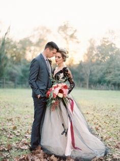 An autumn woodland wedding styled shoot with rich jewel tones in burgundy and emerald green moss, surrounded by fall leaves!