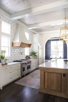 Love the wood island, coffered ceiling, hood vent, backsplash tile