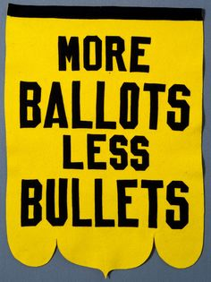 "Women's suffrage banner. Contains yellow felt background with black felt block lettering reading ""MORE/BALLOTS/LESS/BULLETS"". Banner has black felt tape across the top and a scalloped design across the bottom. Circa 1920."