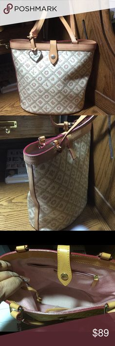 Dooney & Bourke Coated Canvas Signature Bucket Bag A beautiful signature bucket bag made of cream colored coated canvas with tan vachetta leather all beautifully intact.  Hardware is silver but because of the bags color sometimes it looks like brass!  The bag has the Dooney label, key tie, usual pink Dooney tweedish lining all clean and intact.  It has a side zippered pocket with the leather trimmed phone pocket.  It also has a beautiful heart fob.  There is a slight water mark on lower left…