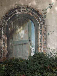 Urban Advertising and Art 000029 - a gem tucked away on the side of a building in Downtown Nashville - an archway with a rustic door slightly open has been painted over brickwork with a white rabbit looking through the gap at the viewer - Nashville, Tennessee