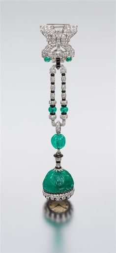 An Art Deco Platinum, Emerald, Diamond, Onyx and Enamel Lapel Watch, Cartier