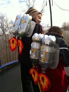 Our version of the DIY rocket packs. 4 soda bottles, silver and glitter paint, red, orange, and yellow felt, a piece of cardboard for the backing, elastic, and decorations. My boys loved these!