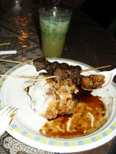 Saté de chèvre. Indonesian food: sate kambing (goat satay) with lontong (sticky rice) and a glass of cendol (cocosmilk sweetened with gula jawa (palmsuger))