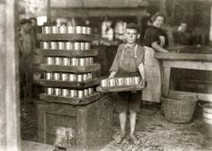 "July 1909. Baltimore, Md. ""One of the small boys in J.S. Farrand Packing Co. and a heavy load. J.W. Magruder, witness."" Photo: Lewis Wickes Hine"