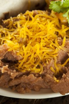 Recipe including course(s): Side; and ingredients: beans, enchilada sauce, fat-free cheddar cheese, onion