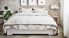 Hvit seng med sengetøy i beige og hvitt.