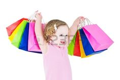 Adorable little girl with curly hair wearing a pink dress is happy after sale and special offer shop Stock Photo