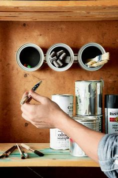 Create storage for pencils or brushes: Place adhesive-backed magnets on the bottoms of small paint cans (use a hot-glue gun for extra hold). Attach to an inexpensive magnetized knife strip on the wall. | Photo: Ryan Benyi