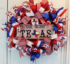 """God Bless Texas"" DecoMesh Wreath with Red, White, and Blue Bows. Celebrate your Texas Pride!!! A custom wooden sign adorns this wreath. Shiny red DecoMesh serves as the base. Including a special Texas ribbon, there are 9 varieties of ribbon ranging from 1 1/2 to 2 1/2 inches wide. All ribbon has a wire edge to allow for you to adjust after shipping. The wreath is approximately 22 inches wide, 22 inches high and 6 inches deep. A few of the ribbon streamers may extend beyond these..."