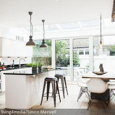 """Eine Backsteinwand verleiht dieser offenen Wohnküche Loft-Charakter. """"Eames Chairs"""" säumen den eleganten Esstisch. Zusätzlichen Platz bietet die großzügige…"""