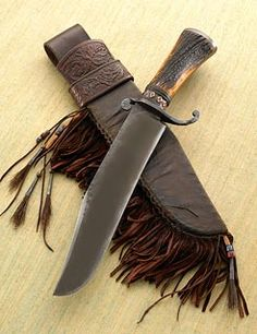 "By Daniel Winkler: Large Bowie with Wrought Iron ""S"" guard and Cap, Full tang Elk Antler handle with patterned copper ferrule and accents. The Tooled Latigo Sheath is covered with Rawhide and is heavily decorated with beads, tin cones and horse hair. Blade - 10 3/4"" Overall - 16 1/4"""