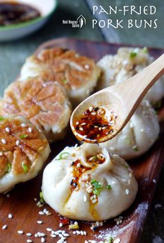 Pouring chilli oil onto freshly cooked Sheng Jian Bao, the popular Shanghai pan-fried pork buns.