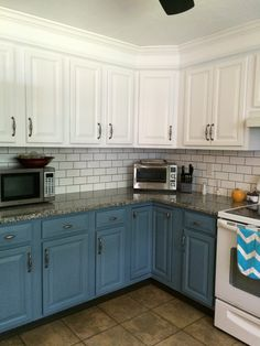 DIY home makeover | modern kitchen | white subway tile backsplash light grey grout | painted white upper cabinets | painted blue lower cabinets | granite countertops | crown molding