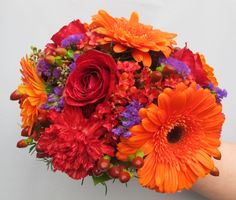 Posy wedding bouquet with orange gerbera daisies, red roses, red carnations, purple statice, hypercium berries and red kalanchoe floral@kuhlmanns.com