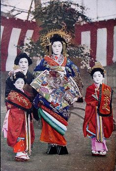 Taisho period (1912-1926), when girls were still recruited from childhood. Until becoming prostitutes in their teens, they acted as pages to the Oiran and were known as kamuro.  Postcards like these were very popular both in Japan and outside, where the protagonists were often mistaken for geisha. In many cases, the beauty of the pictures, the costumes, the pomp and circumstance entirely fail to mask the tragedy that can still be read on those ostensibly blank white faces.