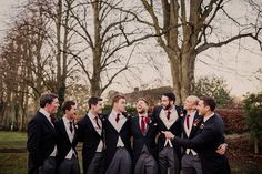 Groomsmen in traditional morning suits with red cravats - Image by Lola Rose Photography - A Winter Wedding in a Tipi with Lace Fishtail Annasul Y Wedding Dress, Jenny Packham Headpiece & Rachel Simpson Shoes. Bridesmaids wear Red Dresses & Cream Fur Stole's and Groomsmen in Traditional Morning Suits.