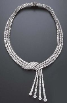 A SPECTACULAR DIAMOND NECKLACE   Designed as graduated baguette-cut diamond articulated lines, gathered at the front by a pavé-set diamond ribbon motif, extending a cascade of baguette-cut diamond tassels, each terminating with a circular-cut diamond, further enhanced by a trillion and bullet-cut diamond clasp, mounted in platinum and 18k white gold, 15½ ins., with French assay marks
