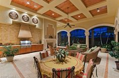 Extensive outdoor living space with summer outdoor kitchen, dining table, ceiling details and lake and golf course views.  Old World Tuscan Masterpiece Home for Sale in the Estates at Grey Oaks | Naples, Florida