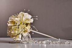 Check out this bouquet made in the Lotus Scepter from Fitz Design with the Sunbeam bouquet accent and a Crystal Garland from Pioneer. All available at: www.pioneerwholesaleco.com. Design by Tom Bowling, AIFD, PFCI. Perfect for a Flower Girl!