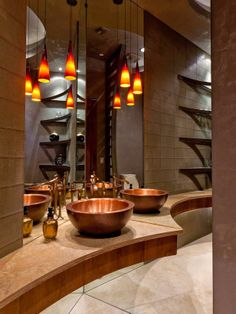 Getting to the Point - In the bathroom's signature touch, a dramatically curved quartz slab top with a wooden apron comes to a point, giving this bath a personality of its own while showcasing the copper sinks and bronze fixtures