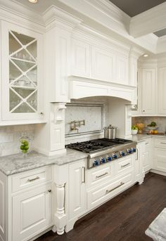 White cabinetry, marble countertops, clear view cabinets, pot filler faucet, dark wood floors | Kitchen Kraft