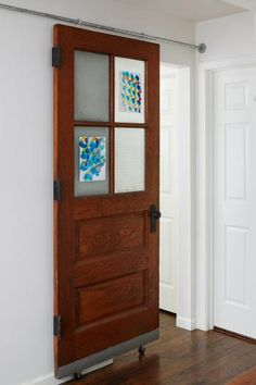 This vintage door that was transformed into a sliding door, allowing for privacy between rooms without having to add another door in crowded space. The sliding door takes up no room at all, and its frosted glass panels double as frames for kids' artwork. | Living the Country Life | http://www.livingthecountrylife.com/homes-acreages/country-homes/18-creative-ways-repurpose-vintage-doors/