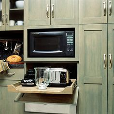 """""""A flip-down door below the microwave reveals a gliding shelf for small appliances.""""  Could be plugged into same outlet as microwave and used in place, not just stored there."""