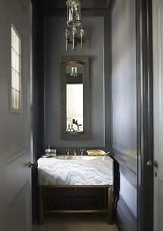 I adore the silver travertine set off by the dramatic paint color. Powder room by S.R. Gambrel.