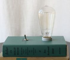 """Features a 30W antique reproduction bulb (squirrel cage or radio style), and a toggle switch for on/off control. As always, the bottom of the lamp is flat so you can stack it with other books, stand it up against the wall, or leave it by itself (it certainly has enough character to be placed on it's own). Book Featured: """"Archer in Hollywood"""" by Ross Macdonald, 1967"""