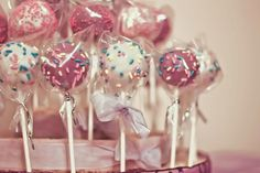 Chocolate and red velvet cake pops decorated with purple coating and sprinkles.