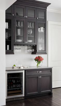 Small butler's pantry with gray quartz countertop and dark stained cabinets. Summit Signature Homes, Inc. Denise Hauser Design Co.